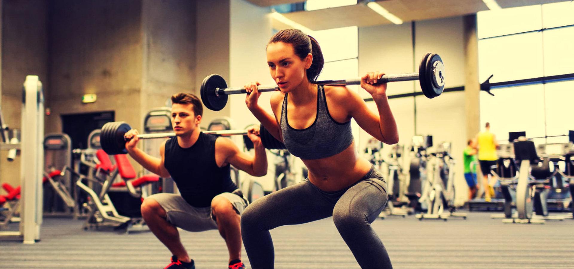 man and woman lifting barbel